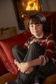 年轻的男孩坐在沙发上舒适日志火 — 图库照片