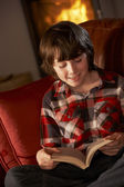 Young Boy Relaxing With Book By Cosy Log Fire — Stock Photo