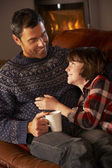 Father And Son Relaxing With Hot Drink By Cosy Log Fire — Stock Photo