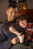 Father And Son Relaxing With Hot Drink Watching TV By Cosy Log F — Foto Stock