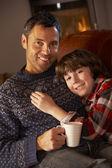Pai e filho relaxante com quente bebida assistindo tv por acolhedor log f — Foto Stock