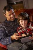 父亲和儿子舒适日志火使用平板电脑 — 图库照片