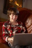 Genç çocuk rahat rahat günlük ateş tarafından dizüstü bilgisayar ile — Stok fotoğraf