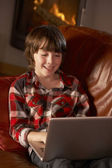 Young Boy Relaxing With Laptop By Cosy Log Fire — Foto Stock