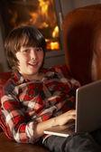 Jovem rapaz relaxante com laptop pela acolhedora lareira — Foto Stock