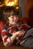Młody chłopak relaksujący z komputera typu tablet przez przytulnym kominkiem — Zdjęcie stockowe