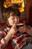 Joven relajante con bebida caliente por la chimenea acogedora — Foto de Stock