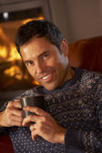 Middle Aged Man Relaxing With Hot Drink By Cosy Log Fire — Foto Stock