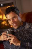 średniej wieku człowiek relaksujący z gorącego napoju przez przytulnym kominkiem — Zdjęcie stockowe