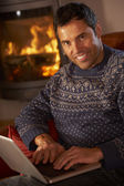 Middle Aged Man Using Laptop Computer By Cosy Log Fire — Stock Photo