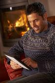 Alter mann mittleren einsatz von tablet pc durch gemütliche kaminfeuer — Stockfoto