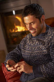 Middle Aged Man Using MP3 Player By Cosy Log Fire — Zdjęcie stockowe