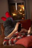 Young Boy Relaxing With MP3 Player By Cosy Log Fire — Stock Photo