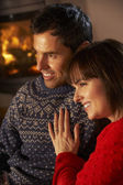 Middle Aged Couple Sitting Sofa Watching TV By Cosy Log Fire — Foto Stock