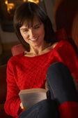 Mulher envelhecida média relaxante com livro por acolhedora lareira — Foto Stock