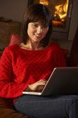 średniej wieku kobieta przy użyciu komputera przenośnego przez przytulnym kominkiem — Zdjęcie stockowe