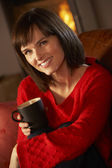 Middle Aged Woman Relaxing With Hot Drink By Cosy Log Fire — Стоковое фото