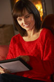 Middle Aged Woman Using Tablet Computer By Cosy Log Fire — Stockfoto