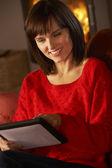 średniej wieku kobieta przy użyciu komputera typu tablet przytulnym kominkiem — Zdjęcie stockowe