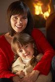 Matka i córka relaksujący na kanapie przy przytulnym kominkiem — Zdjęcie stockowe