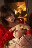 Mãe filha doente reconfortante no sofá pelo log acolhedor de fogo — Foto Stock