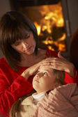 Mother Comforting Sick Daughter On Sofa By Cosy Log Fire — Stock Photo