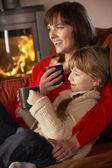 Mutter und tochter, die entspannend, mit warm trinken vor dem fernseher gemütlich — Stockfoto