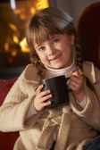 Young Girl Relaxing With Hot Drink By Cosy Log Fire — Stock Photo