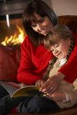 Mãe e filha sentado no sofá e ler o livro pelo log acolhedor — Foto Stock