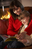 Mother And Daughter Sitting On Sofa And Reading Book By Cosy Log — Zdjęcie stockowe