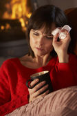 Sick Woman With Cold Resting On Sofa By Cosy Log Fire — Stock Photo