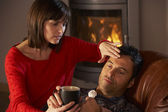 Wife Nursing Sick Husband With Cold Resting On Sofa By Cosy Log — Stockfoto