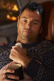 Sick Man With Cold Resting On Sofa By Cosy Log Fire — Stock Photo