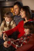 Familie vor dem fernseher mit gemütlichen kaminfeuer entspannen — Stockfoto
