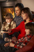 放松的舒适日志火看电视的家庭 — 图库照片