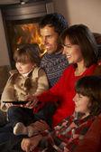 Familia relajarse viendo la televisión por la acogedora chimenea — Foto de Stock