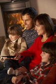 Family Relaxing Watching TV By Cosy Log Fire — Zdjęcie stockowe