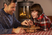 Father And Son Playing Chess By Cosy Log Fire — Стоковое фото