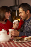 Couple Enjoying Tea And Cake By Cosy Log Fire — Stock Photo