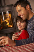 Middle Aged Couple Sitting On Sofa Watching TV By Cosy Log Fire — Stock Photo