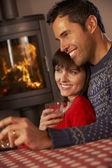 średniej wieku para siedzi na kanapie oglądając tv przez przytulnym kominkiem — Zdjęcie stockowe