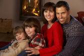 Retrato de familia relajante en sofá por acogedora chimenea — Foto de Stock