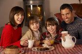 Retrato de familia disfrutando de té y pasteles por acogedora chimenea — Foto de Stock