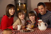 Portrait Of Family Enjoying Tea And Cake By Cosy Log Fire — Stock Photo