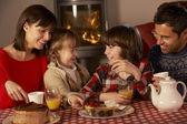 Retrato de família desfrutando de chá e bolo pela acolhedora lareira — Foto Stock