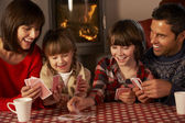 Portrait Of Family Playing Cards By Cosy Log Fire — Stockfoto