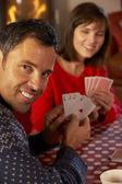 Cartas de jogar de casal pelo log acolhedor de fogo — Foto Stock