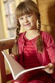 年轻的女孩坐在木制座椅读的书 — 图库照片