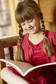 Joven sentada en el asiento de madera libro — Foto de Stock