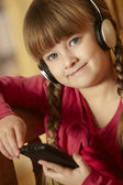 Young Girl Sitting On Wooden Seat Listening To MP3 Player — Stock Photo